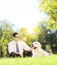 Young man sitting on grass next to a dog in a park on a sunny da green labrador retriever day shot with tilt and shift lens Royalty Free Stock Photo