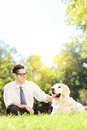 Young man sitting on grass next to his dog in a park on a sunny green labrador retriever day Stock Photo