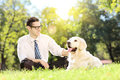 Young man sitting on a green grass next to a dog in a park labrador retriever Royalty Free Stock Photos