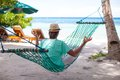 Young man sitting in hat in the lotus position in hammock this image has attached release Royalty Free Stock Image