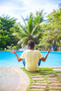 Young man sitting in the lotus position near the swimming poo Royalty Free Stock Photos
