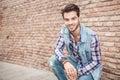 Young man sitting near a brick wall Royalty Free Stock Photo