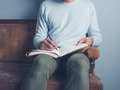 Young man sitting on old sofa writing Royalty Free Stock Photo