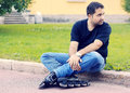A young man sitting in roller skates summer on the curb Royalty Free Stock Photography
