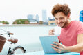 Young man sitting on roof terrace using digital tablet whilst holding cup of coffee smiling Royalty Free Stock Photos