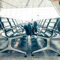 Young man sleeping at the airport while waiting for delayed flights Royalty Free Stock Photos