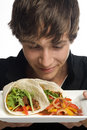 Young man smelling plate of fresh tacos Royalty Free Stock Images