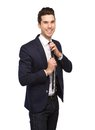 Young man smiling and adjusting necktie portrait of a on isolated white background Royalty Free Stock Photography
