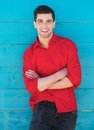 Young man smiling outdoors against blue wall portrait of a Royalty Free Stock Photos