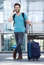 Young man smiling with suitcase at airport Royalty Free Stock Photo
