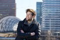Young man smiling with winter jacket in the city close up portrait of a Royalty Free Stock Images