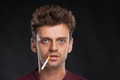 Young man smoking cigarette on black background handsome with brown hair wearing red t shirt Stock Photo