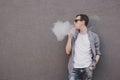 Young man smoking, vaping electronic cigarette or vape. Gray background Royalty Free Stock Photo