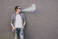 Young man smoking, vaping electronic cigarette or vape. Gray background Royalty Free Stock Photo