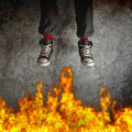 Young man in sneakers is jumping over fire flames concept of recklessness and risk Royalty Free Stock Images