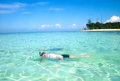 Young man snorkeling next to tropical island a beautiful Royalty Free Stock Images
