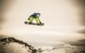 Young man snowboarder high trick jump Royalty Free Stock Image