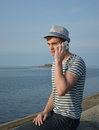 Young man speaking on a cell phone the in the hat and striped t shirt sitting the parapet in front of the sea Stock Photo