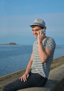 Young man speaking on a cell phone and smiling the in the hat striped t shirt sitting the parapet in front of the Royalty Free Stock Photography