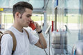 Young man speaking on public phone in station Royalty Free Stock Photo