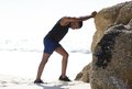 Young man sport training exercise stretching legs at the beach Royalty Free Stock Photo