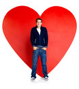 Young man standing against a big red heart Royalty Free Stock Photography