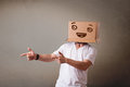 Young man standing and gesturing with a cardboard box on his head with smiley face Stock Photos
