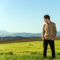 Young man standing in green field. Stock Images