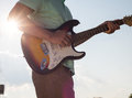 Young man standing with a guitar on background of sky and sunlight Royalty Free Stock Photo