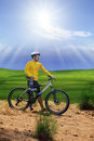 Young man standing beside moutain bike ,mtb on hill with sun shi Royalty Free Stock Photo