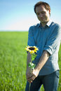 Young man standing with a sunflower