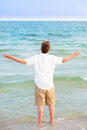 Young man standing in surf with arms up blue ocean open wide Stock Photos