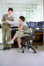 Young man standing by young woman sitting by desk in office, looking at paperwork, smiling Royalty Free Stock Photo