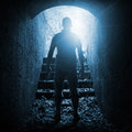 Young man stands in dark stone tunnel blue toned with glowing end square photo Stock Images