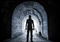 Young man stands in dark tunnel and looks the glowing end Stock Photos