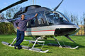 Young man stands next to small helicopter Royalty Free Stock Image