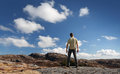 Young man stands on rocky ground staring at blue sky Stock Photo