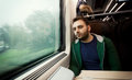 Young man staring out the train window. Royalty Free Stock Photo