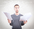 Young man stressed holding papers on grey background Royalty Free Stock Photo