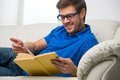 Young man stretching comfortably on couch guy reading book and relaxing at home Royalty Free Stock Photo