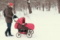 Young man strolling pushchair with baby in winter park Royalty Free Stock Photo