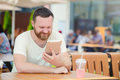 Young man student using a tablet computer in a cafe with a cool drink in the city. Royalty Free Stock Photo
