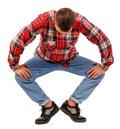 Young man performing plie on the first swivel position, in a checkered shirt, isolated on white background