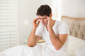 Young man suffering from headache in bed side view of a at home Stock Photography