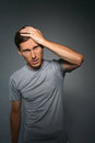 Young man suffering from a headache, a gesture of annoyance. Royalty Free Stock Photo