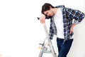 Young man suffering while working on a stepladder view of Stock Image