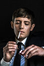 Young man in a suit smoking a cigarette Stock Photo