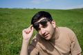 Young man in sunglass handsome close up portrait with a on a green meadow Stock Photo