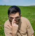 Young man in sunglass handsome close up portrait with a on a green meadow Stock Image