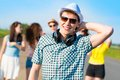 Young man in sunglasses men a hat holds a hand on a background of blue sky and friends Royalty Free Stock Photo